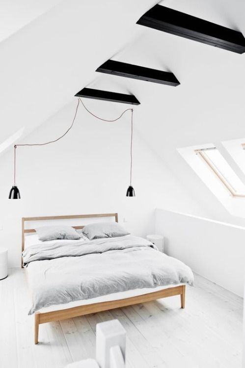 a light-filled and airy attic bedroom with black ceiling beams and black pendant lamps for more drama