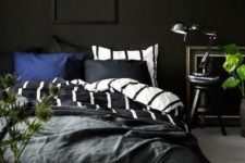 09 a moody bedroom with black walls, vintage finds and touches of fresh greenery for freshness
