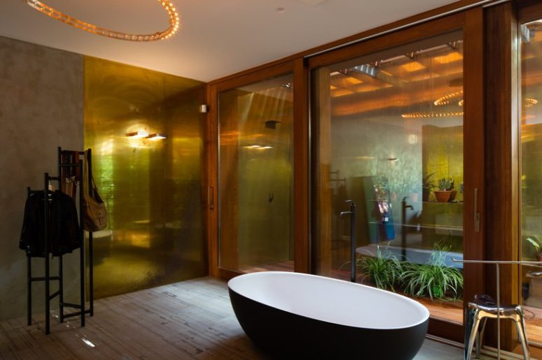 The bathroom features glazing, too, but the privacy is kept with an outdoor garden