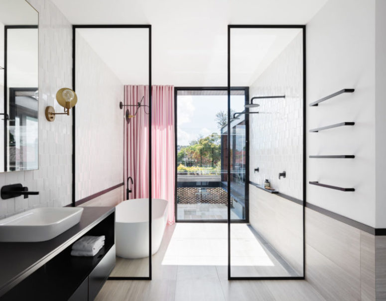 The bathroom is light-filled, airy and spacious accented with black touches and a pink curtain