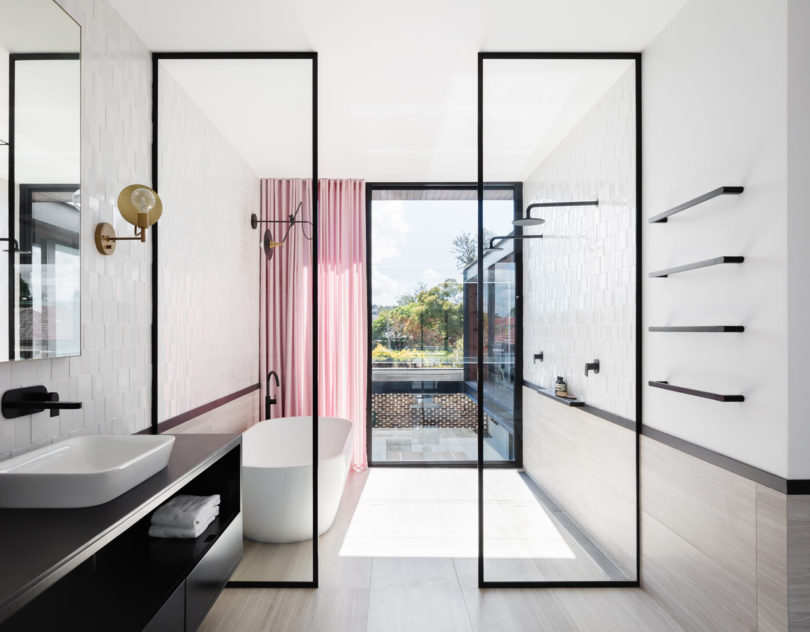 The bathroom is light filled, airy and spacious accented with black touches and a pink curtain