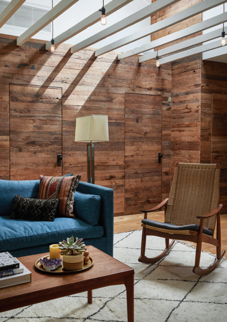 This space is done with weathered and rustic wood, there's a cool woven chair and a blue sofa