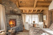 a cabin bedroom with touches of wood and stone, with faux fur and metal chandelier