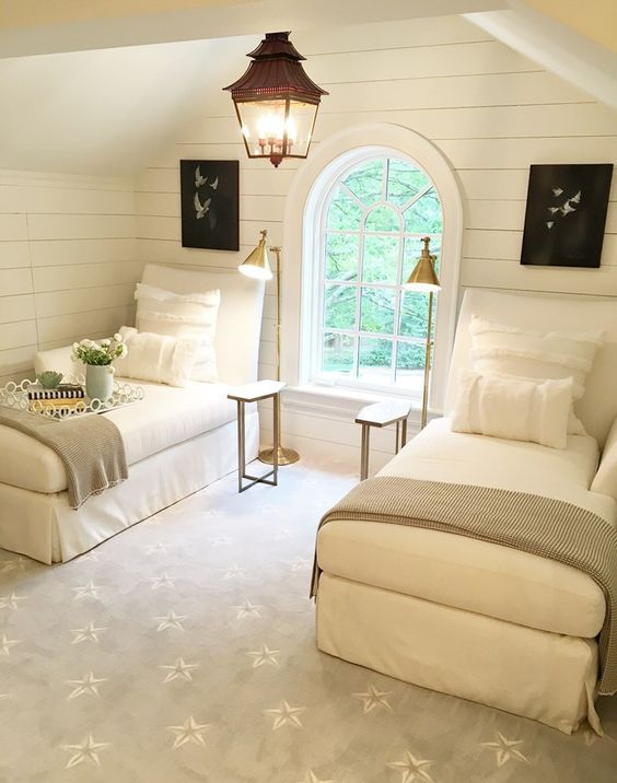 a cozy vintage inspired guest bedroom with two beds, brass lamps and an arched window