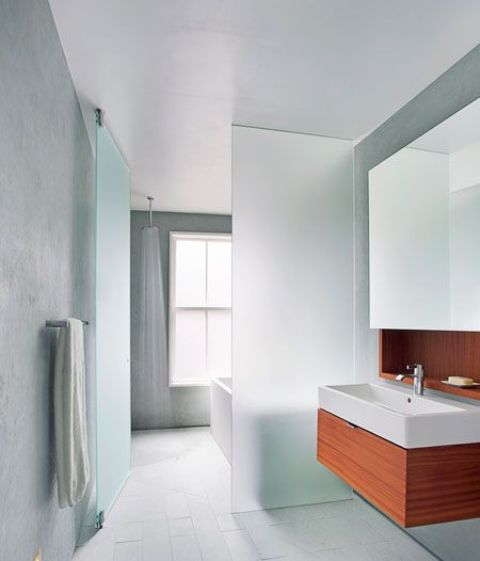 a plane of frosted glass separates the wet side of the bathroom, with the open shower, from the dry side
