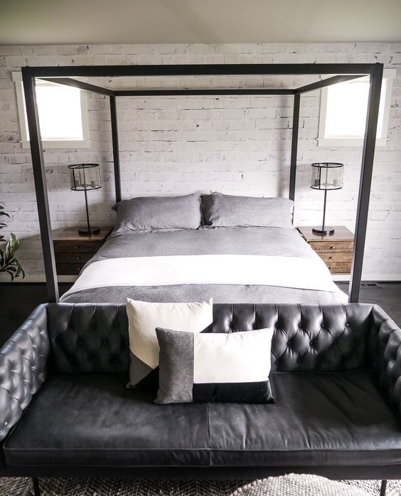 an industrial bedroom with a black leather tufted sofa at the foot of the bed that adds style