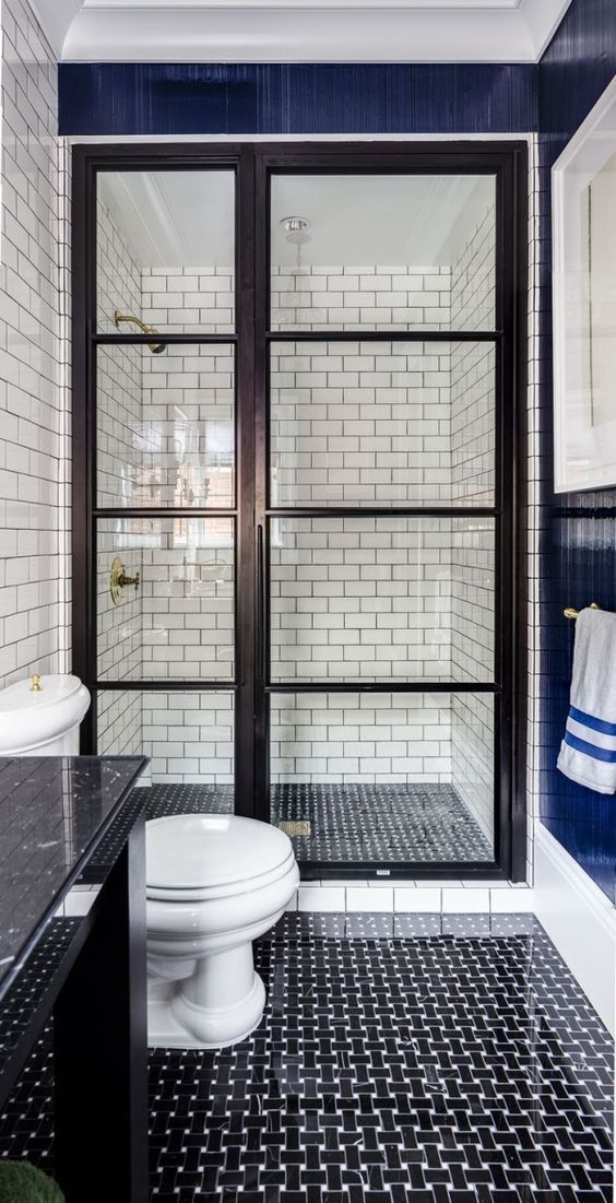 black and white graphic tiles on the floor, white subway tiles with black grout on the walls in a walk-in shower