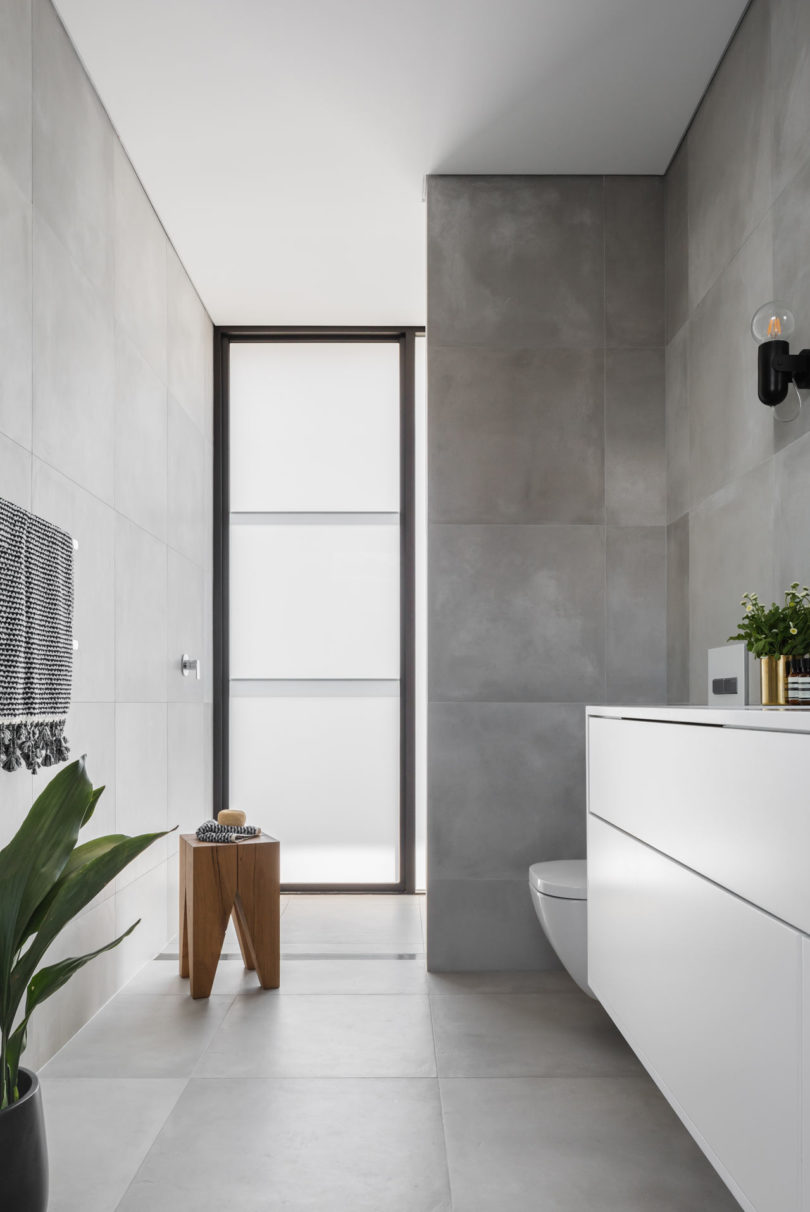 Another bathroom features concrete iles and a frosted glass window