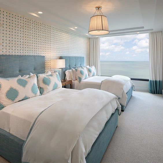 a fantastic guest bedroom with two large beds and a gorgeous panoramic sea view