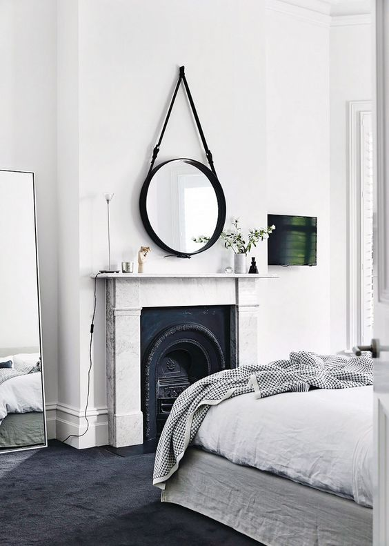 a fireplace as a centerpiece of the bedroom, done with wrought details and a chic stone mantel