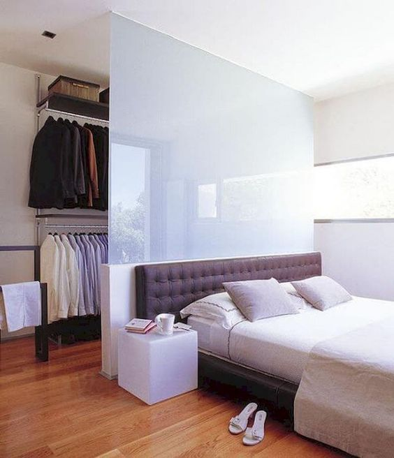 a half wall of frosted glass gently separates the closet from the bedroom, keeps it hidden but not too much