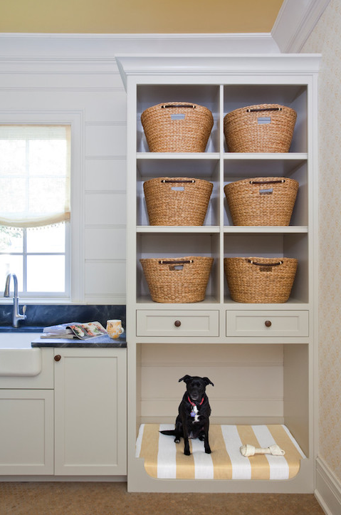 a laundry room with an open storage cabinet and a pet bed incorporated into its lower part