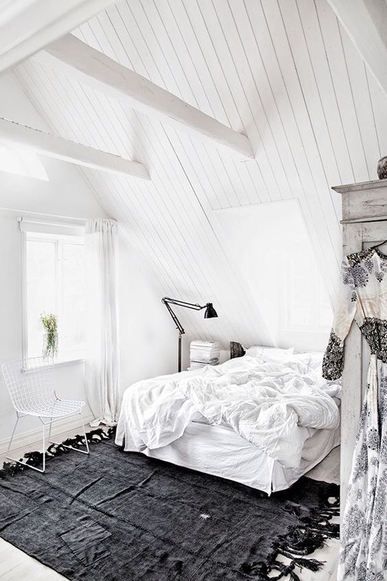 a totally white attic bedroom with a floating bed, much light and a single black rug for a contrast