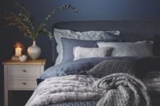 11 a very cozy bedroom with a navy wall and navy and white bedding and blankets