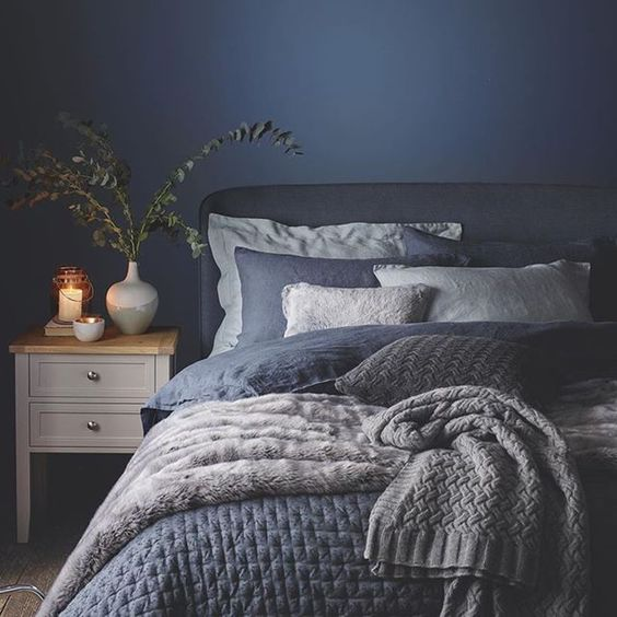 a very cozy bedroom with a navy wall and navy and white bedding and blankets