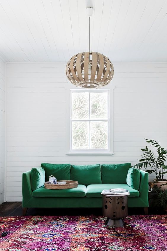 an emerald sofa will definitely make a bold statement in the living room and accent the space a lot