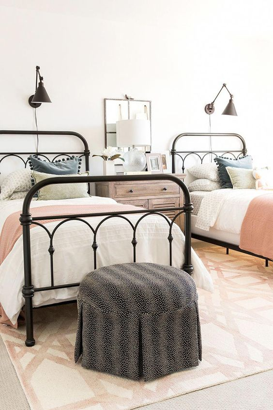 a farmhouse guest bedroom with two beds and touches of various muted colors