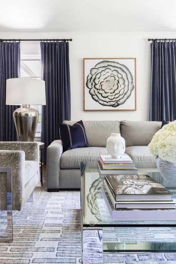 a stylish living room with grey furniture and navy pillows and curtains create a very chic and refined look