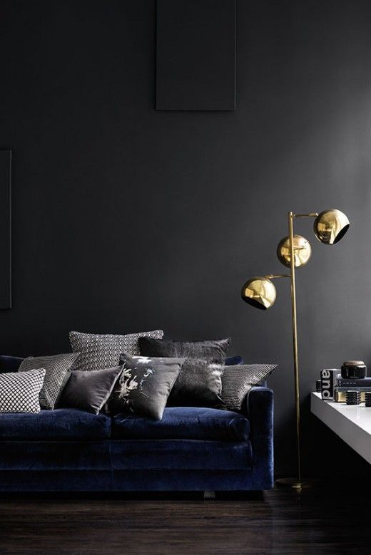 a dark living room design with a blue sofa