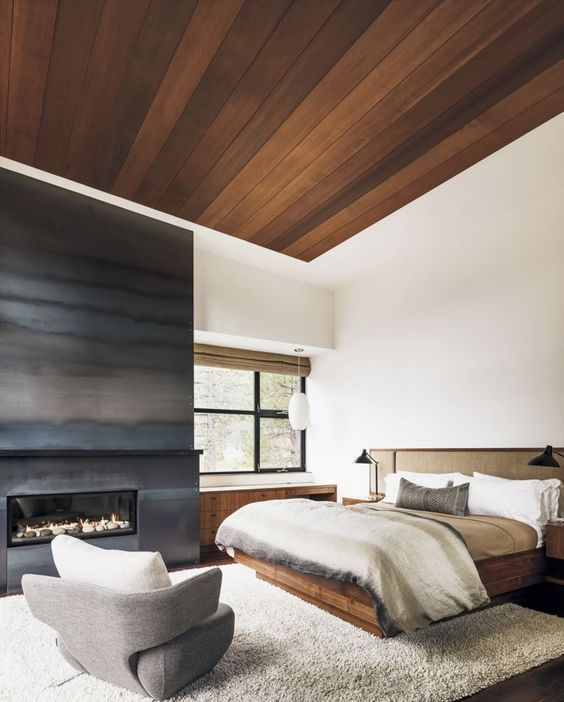 a fireplace completely covered with darkened metal is a gorgeous statement for a neutral bedroom