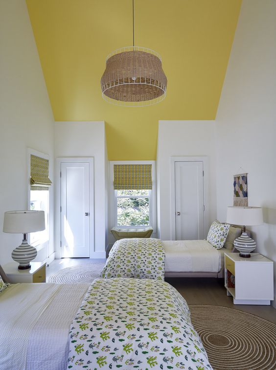 a lively twin guest bedroom with sunny yellow touches, printed textiles and several windows