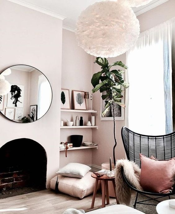 a cozy girlish bedroom with a brick clad built in fireplace and a round mirror over it