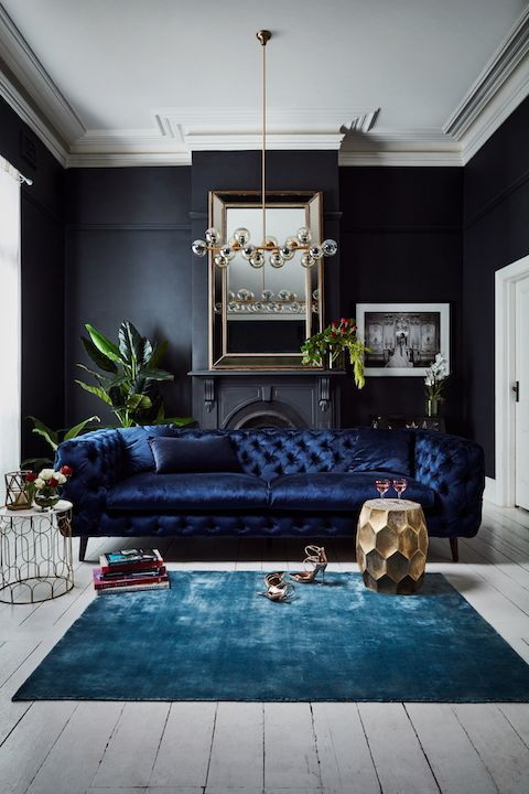 a fantastic and refined navy tufted velvet sofa adds a moody feel  and texture to the room