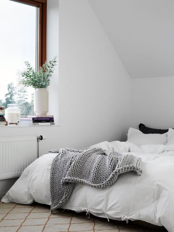 a minimalist attic bedroom done in mixed neutrals, with touches of black