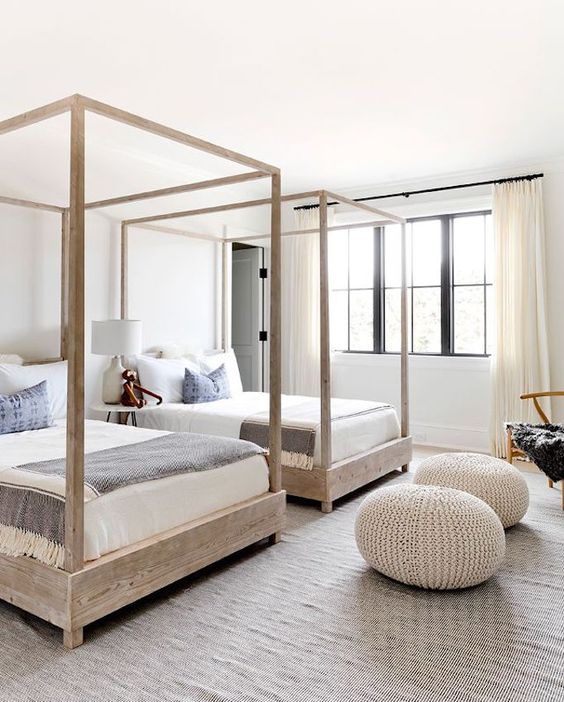 a modern beach twin guest bedroom with canopy beds, knit ottomans and much natural light