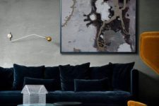 14 a sophisticated living room with grey walls and a floor, with a large refiend navy velvet sofa and pillows