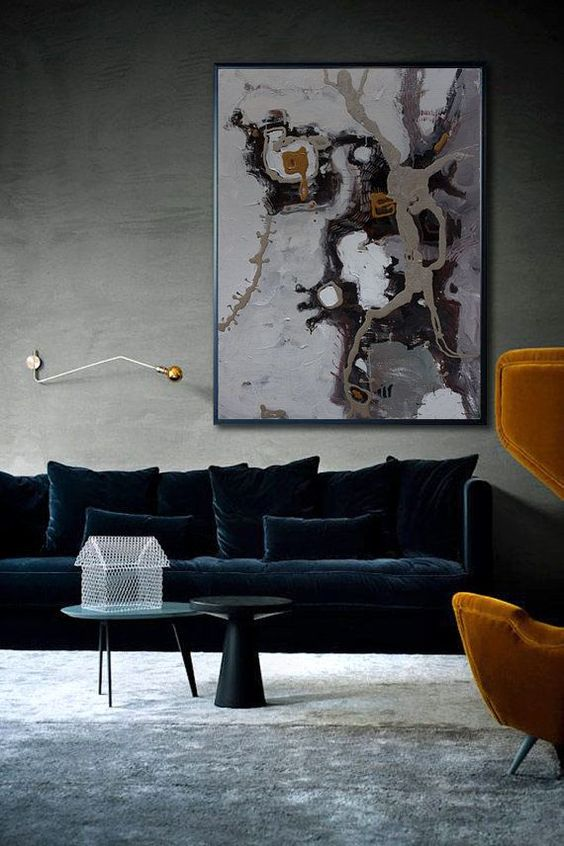 a sophisticated living room with grey walls and a floor, with a large refiend navy velvet sofa and pillows