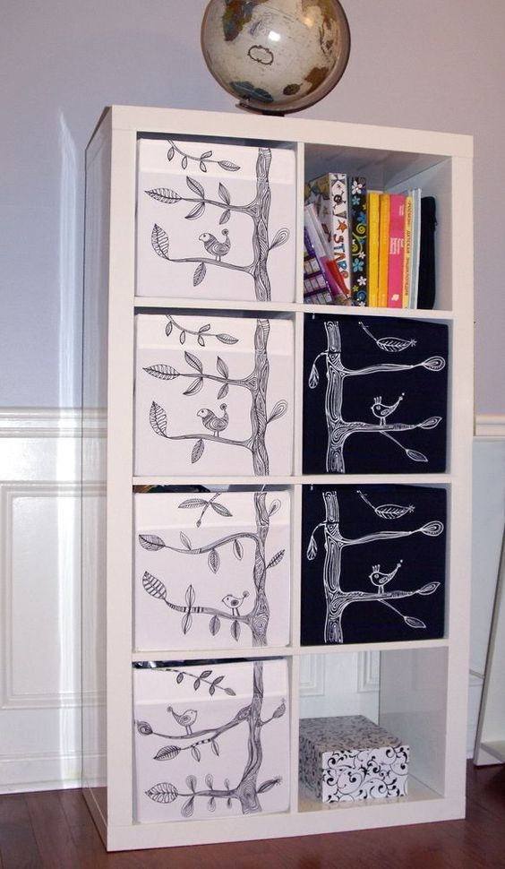 a white Expedit shelf with Drona storage boxes and cute EIVOR patterns of birds and trees