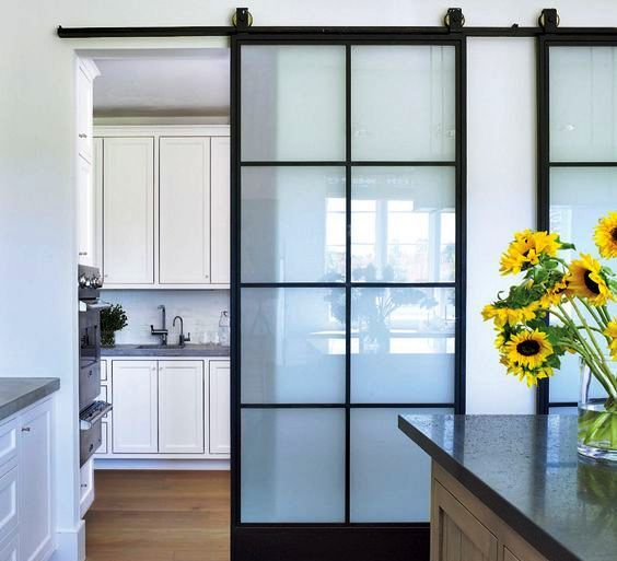 sliding doors with black framing and frosted glass divide the kitchen and the dining space very comfortably