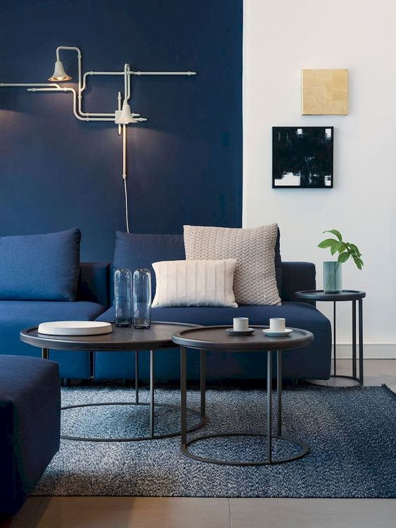 a living room with a navy statement wall, a navy sofa and a grey rug plus coffee tables
