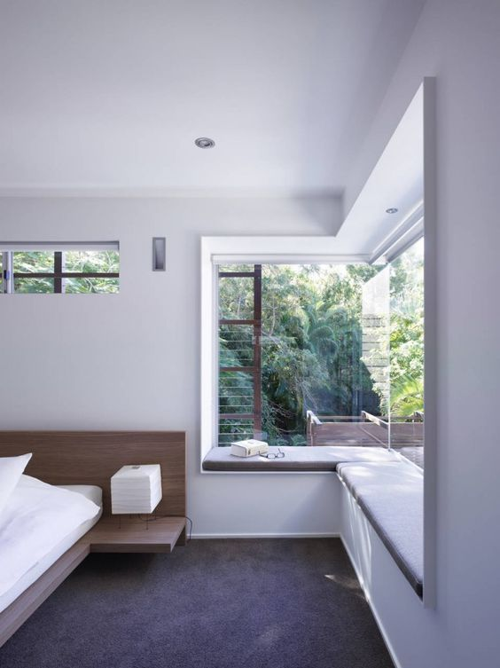 a minimalist bedroom with an upholstered windowsill as a daybed or a seat is a cool idea to catch the views