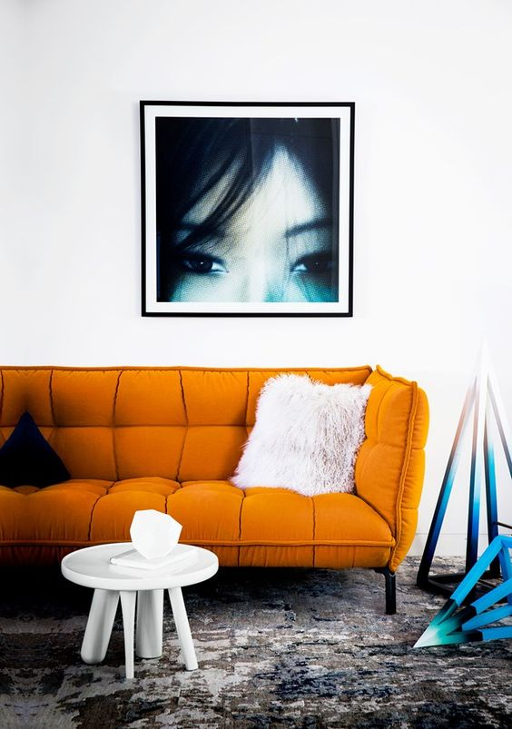 a modern orange sofa makes a statement with its catchy shape and bold color and texture