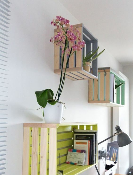 Knagglig boxes painted in bright colors inside and attached to the wall as open storage items