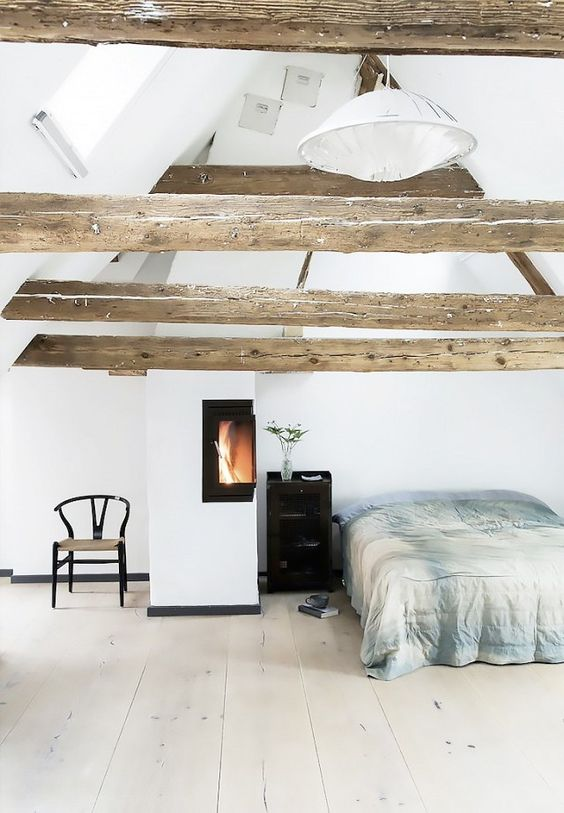 a cozy light filled bedroom with wooden beams on the ceiling and a warming up hearth by the bed