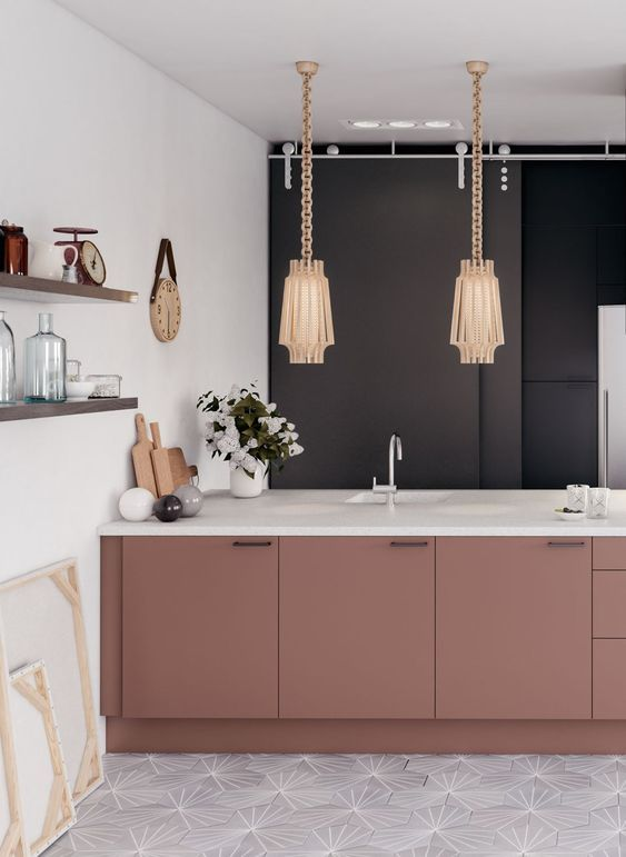 a feminine kitchen done in neutrals and accented with a black wall and dusty pink cabinets plus refined lamps