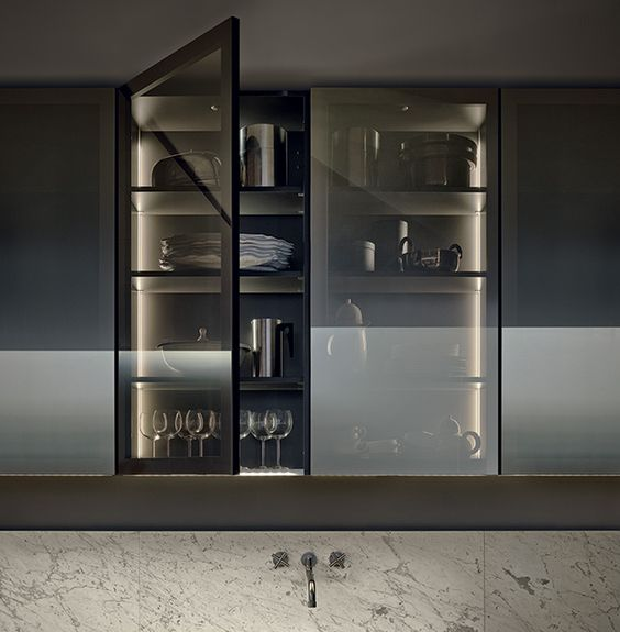 a kitchen cabinet with smoke glass doors shows off the glasses and dishes but does it gently