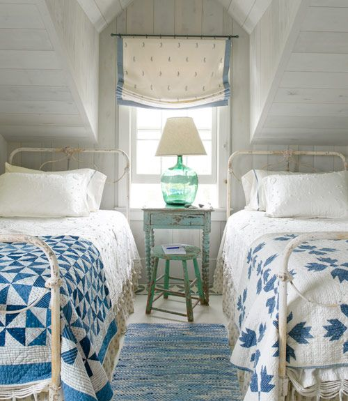 a small attic oceanside guest bedroom with two beds and some shabby chic furniture