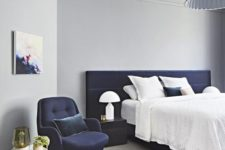 16 an airy bedroom in light grey with a navy upholstered bed and chair for a bold look