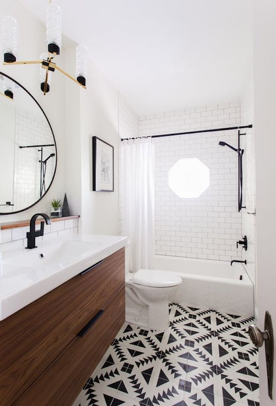 chic black and white mosaic tiles on the floor and white subway tiles with black grout on the walls for a bold look