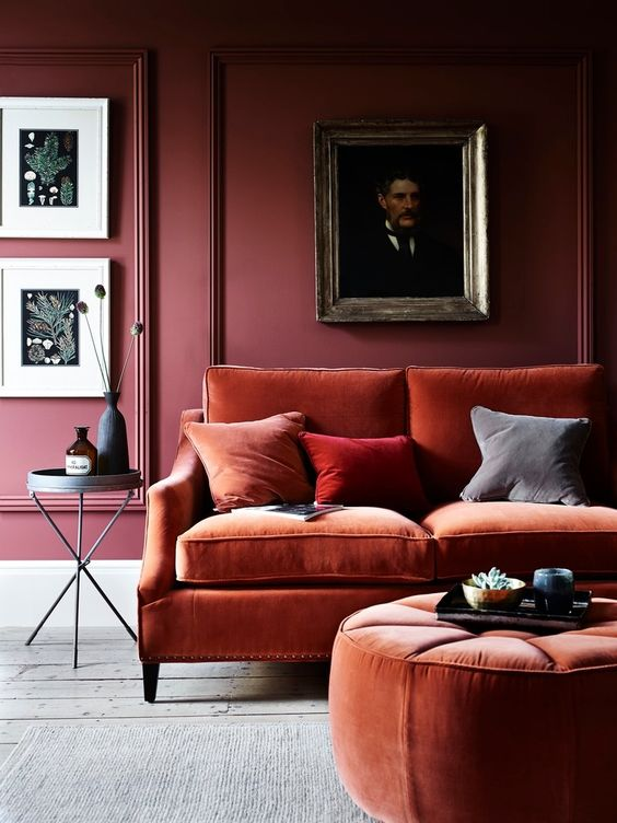 create a color block effect with burgundy walls and rust-colored velvet furniture