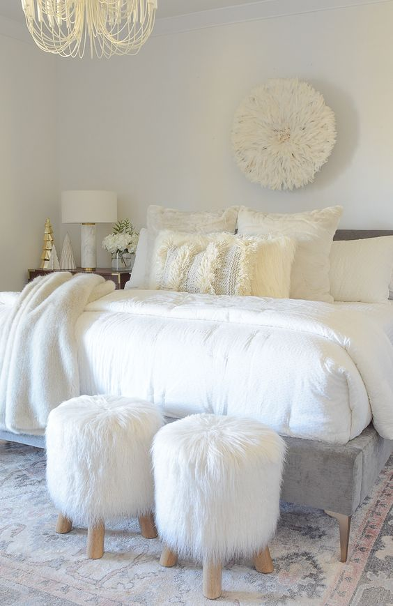 a cozying up printed rug, faux fur stools and fur throw blankets make the bedroom very inviting