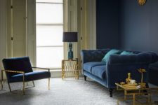 17 a refined living room with a grey floor, a navy wall, a navy sofa and chair