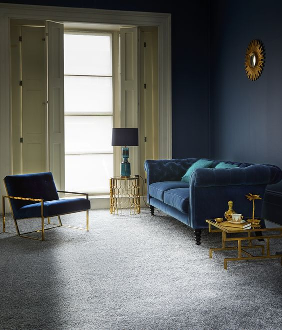 a refined living room with a grey floor, a navy wall, a navy sofa and chair