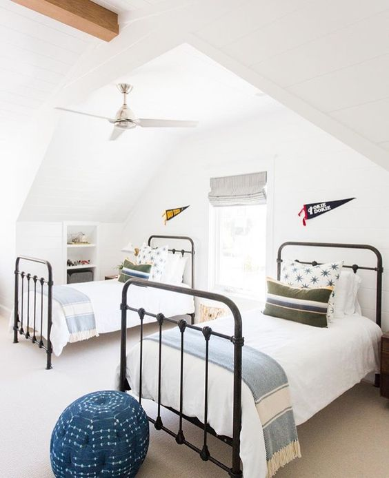 a stylish attic guest bedroom with two beds, a single window with shades and blue touches