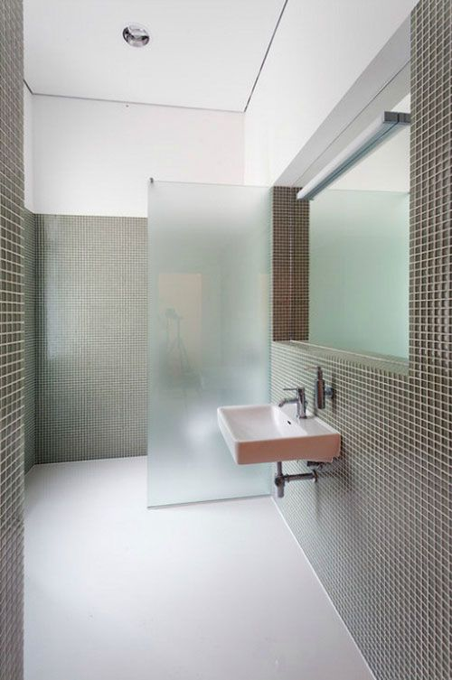 a stylish minimalist bathroom with grey tiles and white grout and a frosted glass space divider for the toilet