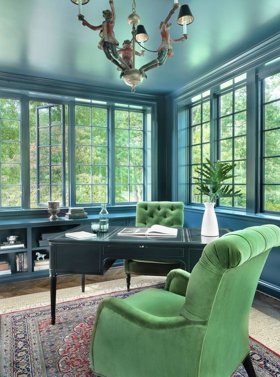 a vintage-inspired elegant blue home office accented with a black desk and green velvet chairs